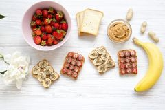 Healthy breakfast with ingredients, dieting concept. Vegan toasts with fruits, seeds, peanut butter over white wooden background,. Top view. From above Royalty Free Stock Image