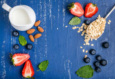 Healthy breakfast ingredients food frame. Oatmeal, milk in creamer, berries, almond and mint on painted blue wooden Royalty Free Stock Images