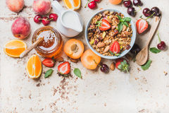 Healthy breakfast ingredients. Oat granola in bowl with nuts, strawberry and mint leaves, milk in pitcher, honey in Stock Image
