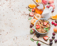 Healthy breakfast ingredients. Oat granola in bowl with nuts, strawberry and mint leaves, milk in pitcher, honey in. Glass jar, fresh fruits and berries on Royalty Free Stock Photos