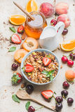 Healthy breakfast ingredients. Oat granola in bowl with nuts, strawberry and mint, milk in pitcher, honey in glass jar Stock Photos