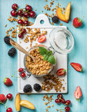 Healthy breakfast ingredients. Oat granola in open glass jar, fruit, berries and mint on blue background with white Royalty Free Stock Image