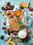 Healthy breakfast ingredients. Oat granola in open glass jar, yogurt, fruit, berries, honey and mint on blue background Royalty Free Stock Image