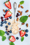 Healthy breakfast ingredients. Oatmeal, berries, almond and mint leaves on painted blue wooden background Stock Images