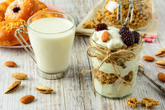 Healthy breakfast ingredients on a white wooden table. Healthy breakfast ingredients. Homemade granola with yogurt in open glass jar, milk and fresh fragrant stock photo