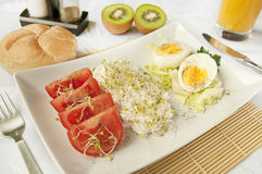 Healthy breakfast - keep the diet. Healthy nutrition - cottage cheese, tomatoes, orange juice, kiwi fruits and hard boiled eggs. Dietary breakfast Royalty Free Stock Images