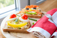 Healthy breakfast for kids: sandwiches with funny faces. Funny sandwiches for kids. Healthy colorful breakfast, lots of vegetables, green salad and whole grain Stock Photos