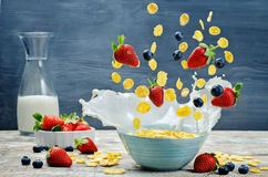 Healthy breakfast with milk, flying corn flakes, strawberries an Royalty Free Stock Photos