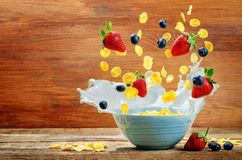 Healthy breakfast with milk, flying corn flakes, strawberries an Stock Photo