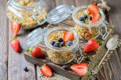 Healthy breakfast of muesli, berries. On dark wood background Royalty Free Stock Photo