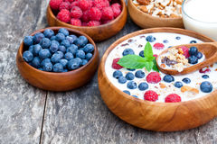 Healthy breakfast muesli with berries and milk in wooden plate. Healthy breakfast muesli  with berries and milk in wooden plate Royalty Free Stock Photos