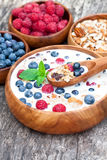 Healthy breakfast muesli with berries and milk in wooden plate Royalty Free Stock Image