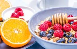 Healthy breakfast. Breakfast with muesli and fresh berries, honey, yogurt, orange on table.Healthy morning food. Health and diet concept Stock Images