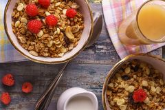 Muesli with raspberry and fresh juice. Healthy breakfast with  muesli, fresh raspberry, fruit juice, jug of milk, flat lay, horizontal Stock Photos