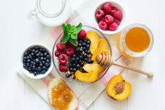 Healthy breakfast: muesli with honey, milk and fresh berries in a bowl Royalty Free Stock Image