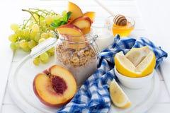 Healthy breakfast: muesli with smoothie, honey, yogurt and fresh berries in a glass jar Stock Image