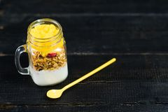 Healthy breakfast muesli and yogurt with mango smoothie in glass mason jars. stock photography