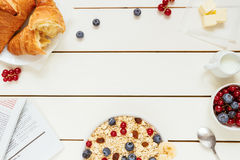Healthy breakfast with oat flakes, berries, croissants on the white wooden table with copy space, top view royalty free stock photo