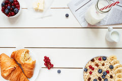 Healthy breakfast with oat flakes, berries, croissants on the white wooden table with copy space, top view royalty free stock image