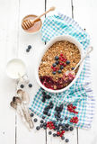 Healthy breakfast. Oat granola berry crumble with. Fresh blueberries, yogurt and honey in ceramic cooking dish over white rustic backdrop, top view stock images
