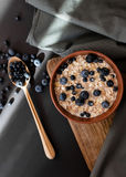 Healthy breakfast. Oat granola with fresh blueberries and currants in a clay bowl over dark grunge surface. royalty free stock photos