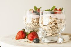 Healthy breakfast, oat meal with fruits: bluebery, strawbery and min, parfait in a glass on a rustic background. Healthy food. Isolated royalty free stock image
