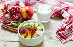 Healthy Breakfast. Oatmeal with banana, peach, nectarine and pomegranate with cinnamon Stock Photography