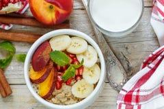 Healthy Breakfast. Oatmeal with banana, peach, nectarine and pomegranate with cinnamon Royalty Free Stock Photos