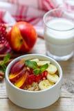 Healthy Breakfast. Oatmeal with banana, peach, nectarine and pomegranate with cinnamon Stock Image