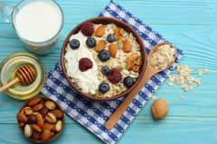 Healthy breakfast. oatmeal, blueberries, raspberries, honey, milk and nuts on blue wooden table. Top view with copy space Stock Photos