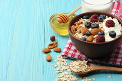 Healthy breakfast. oatmeal, blueberries, raspberries, milk, honey and nuts on blue wooden table Royalty Free Stock Photos