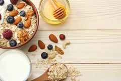 Healthy breakfast. oatmeal, blueberries, raspberries, milk, honey and nuts on white wooden table. Top view with copy space Stock Photos