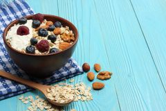 Healthy breakfast. oatmeal, blueberries, raspberries and nuts on blue wooden table Stock Image