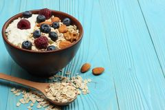Healthy breakfast. oatmeal, blueberries, raspberries and nuts on blue wooden table Royalty Free Stock Photography
