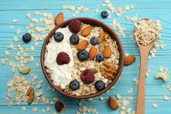 Healthy breakfast. oatmeal, blueberries, raspberries and nuts on blue wooden table. Top view with copy space Stock Photos