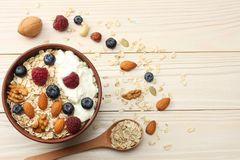 Healthy breakfast. oatmeal, blueberries, raspberries and nuts on white wooden table. Top view with copy space Stock Image
