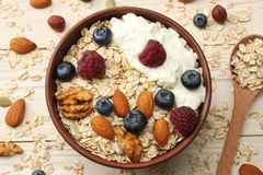 Healthy breakfast. oatmeal, blueberries, raspberries and nuts on white wooden table. Top view Royalty Free Stock Photography
