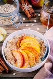 Healthy breakfast: oatmeal bowl with caramelized apples, cinnamon and honey Stock Photos