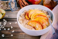 Healthy breakfast: oatmeal bowl with caramelized apples, cinnamon and honey stock photo