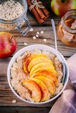 Healthy breakfast: oatmeal bowl with caramelized peaches, cinnamon and honey Royalty Free Stock Photos