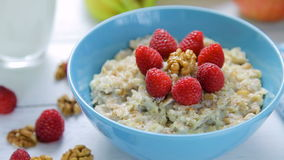 Healthy breakfast - oatmeal with fresh, ripe raspberries and walnuts in a bowl standing on a wooden table stock footage