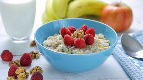 Healthy breakfast - oatmeal with fresh, ripe raspberries and walnuts in a bowl standing on a wooden table stock video footage
