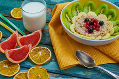 Healthy breakfast with oatmeal and fruit. Granola with kiwi, bananas, berries, grapefruit and a glass of milk. Wooden background. Selective focus Stock Photos