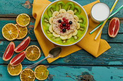 Healthy breakfast with oatmeal and fruit. Granola with kiwi, bananas, berries, grapefruit and a glass of milk. Wooden background. Top view. Selective focus Stock Photography