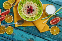 Healthy breakfast with oatmeal and fruit. Granola with kiwi, bananas, berries, grapefruit and a glass of milk. Wooden background. Top view. Selective focus Stock Photo