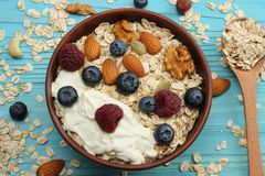 Healthy breakfast. oatmeal, honey, blueberries, raspberries and nuts on blue wooden table. Top view with copy space Stock Photography