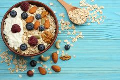 Healthy breakfast. oatmeal, honey, blueberries, raspberries and nuts on blue wooden table. Top view with copy space Stock Image