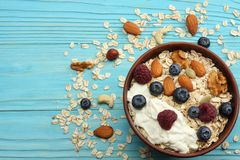 Healthy breakfast. oatmeal, honey, blueberries, raspberries and nuts on blue wooden table. Top view with copy space Royalty Free Stock Photography