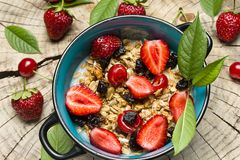 Healthy Breakfast. Oatmeal with muesli and fruit fresh strawberries, cherries and prunes with honey on the cut surface of wood. Oatmeal with muesli and fruit Stock Images