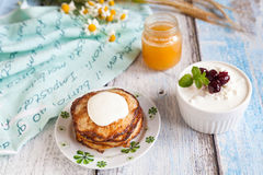Healthy breakfast with oatmeal pancakes, beaded cheese and honey. Breakfast: oatmeal pancakes with sour cream, beaded cheese with chery jam and honey Stock Photo